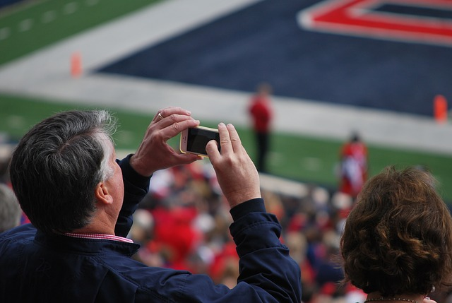 Man taking photo with phone at football game